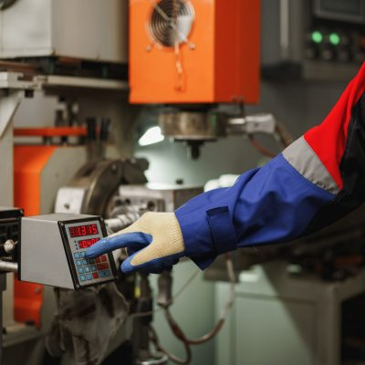 Worker operating a machine in a factory pushing a button, close up